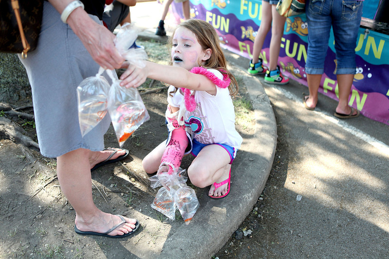 Nine-year-old Emily Robertson of Geneva keeps track of the seven goldfish she won at the carnival during the Swedish Days Festival in Geneva Thursday.