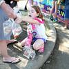 Nine-year-old Emily Robertson of Geneva keeps track of the seven goldfish she won at the carnival during the Swedish Days Festival in Geneva Thursday.