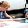 Rosie Antonson, of Geneva, gets some last minute encouragement from her mother before competing in the Super Kids soap box derby race in downtown Geneva as a part of Geneva's annual Swedish Days Festival. Antonson competed against another special needs racer in cars designed for neurotypical children to drive and for special needs children to ride alongside.