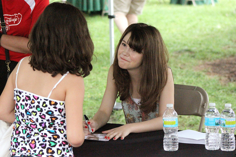 Shealeigh signs an autograph for Olivia Arias, 10, from Genoa, during a meet-and-greet session following her concert on the Center Stage during Geneva's annual Swedish Days Festival. Rain had caused most of the day's events to be canceled or postponed, but Shealeigh was able to take the stage.