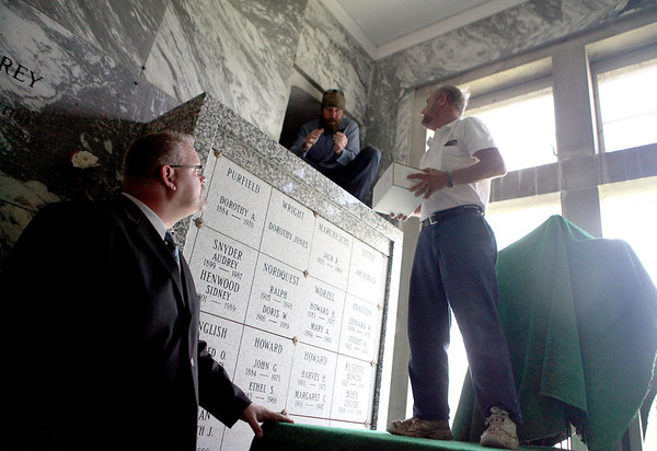 Kane County Coroner Rob Russell (far left) looks on as St. Charles Township Cemeteries Superintendent Roger Ronzheimer and manager Brooks Ronzheimer inter the county's unclaimed cremains during a memorial service at North Cemetery in St. Charles Thursday.