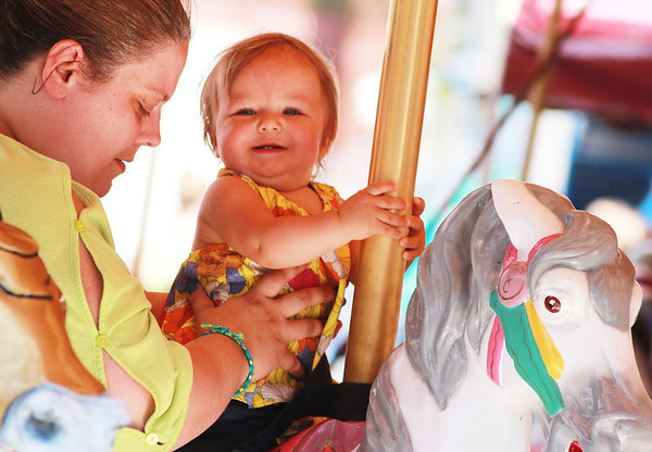 Ashrina Rushani, 14 months, and her mother, Sendie, of St. Charles, enjoy the carousal at the Swedish Days Festival in downtown Geneva Thursday.