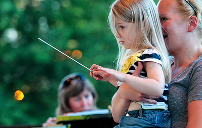 Kyle Grillot - kgrillot@shawmedia.com   Maren Filetti, 4, (left) held by her mother Carrie Filetti, conducts the Woodstock City Band in Woodstock Square  after winning a raffle on June 26, 2013. Now in its 129th season, the band concerts have become a Woodstock tradition. People gather with chairs and blankets to relax in Woodstock square.