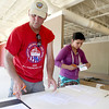Stan Inglehart, a member of Kiwanis Club of Geneva and race director for the inaugural Swedish Days soap box derby, and Kiwanis volunteer Angel Ayala help drivers check in for the race.