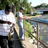 Charles Brooks of Naperville unhooks a fish he caught in the Fox River in Geneva as Rene Gonzales of Campton Hills waits for a catch.