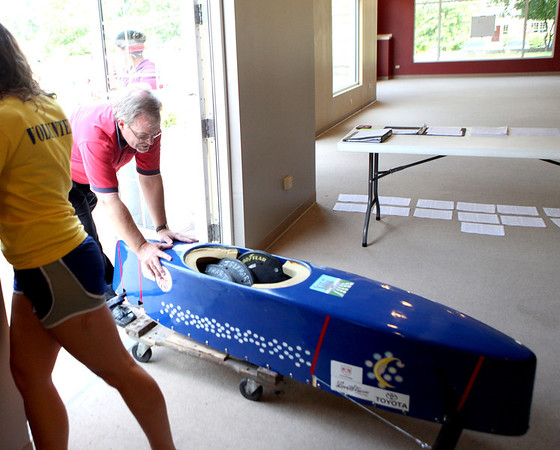 Kiwanis Club of Geneva President Rich Foster moves a soap box derby car into position as it is checked in for the inaugural race during Swedish Days in Geneva.