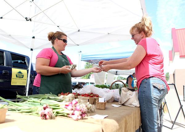 Sue Olszewski of Batavia purchase vegetables from Danielle Stojan of Stojan's Vegetables in Maple Park during the opening day of the season for the Geneva Green Market Thursday.