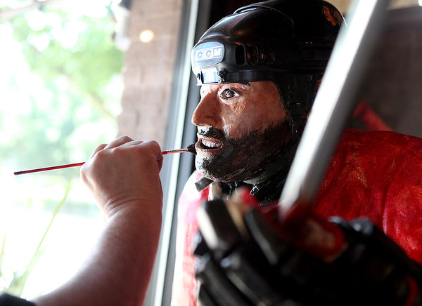 Chef Alain Roby paints a chocolate beard onto his Chicago Blackhawks player, which is made all  of chocolate, at the All Chocolate Kitchen in Geneva Monday.