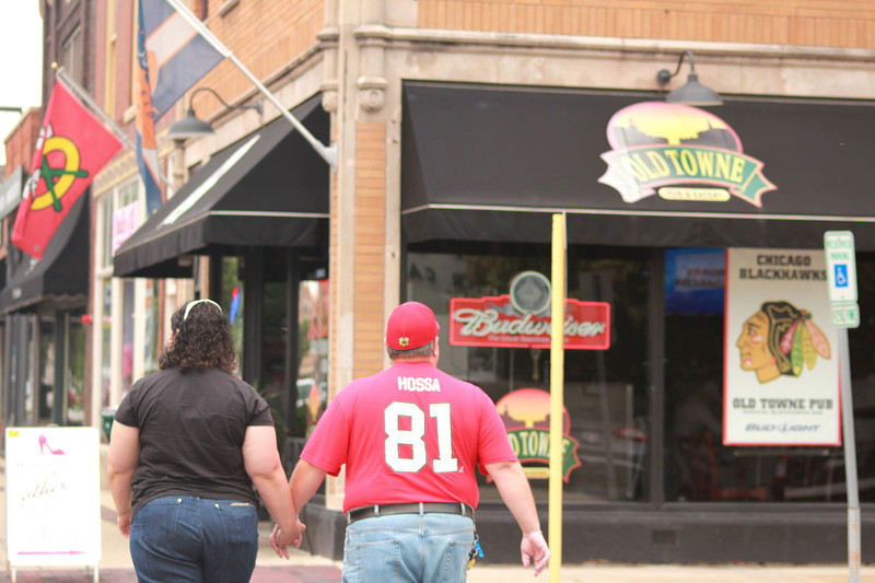 Fans of the Chicago Blackhawks walk past Old Towne Pub & Eatery on West State Street in Geneva Tuesday.