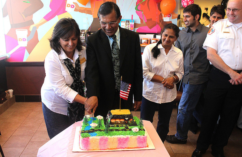 Jay Patel, owner of the St. Charles Dunkin' Donuts located on Main Street, cuts through an ice cream cake with St. Charles Alderman RitaAnne Payleitner during the store's grand re-opening ceremony on Friday. Local officials, as well as representatives from Dunkin' Donuts corporate branch came out to celebrate the store's re-opening.