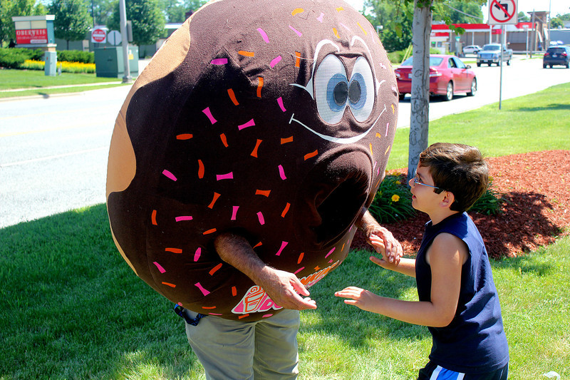 Hayden Haneberg, 8, of St. Charles greets the Dunkin' Donuts mascot outside of the St. Charles store on Main Street during the store's grand re-opening celebration on Friday. Haneberg is a regular customer, he and his mother come to Dunkin' Donuts almost every day.