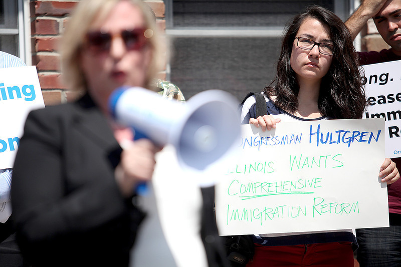 Claire O'Brien of St. Charles holds a sign urging U.S. Rep. Randy Hultgren, R-Winfield, to support comprehensive immigration reform as Jasna Ostojich speaks about her own immigration experience during a press conference outside his Geneva office Thursday. The press conference was hosted by the Chicago and St. Charles chapters of Organizing for Action.