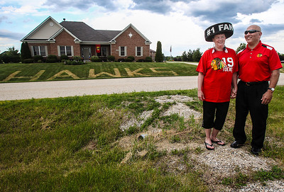 "Sarah Nader - snader@shawmedia.com Chicago Blackhawks fans Jody Spizzirri and her husband, Steve, stand in front of their Lakemoor home before Monday's Blackhawks game on June 17, 2013. The Spizzirri's have been life long fans of the Blackhawks and have started to mow ""GO HAWKS"" in their lawn everything time they make the Stanley Cup Finals. They plan on added a cup to their years when the serious is over."