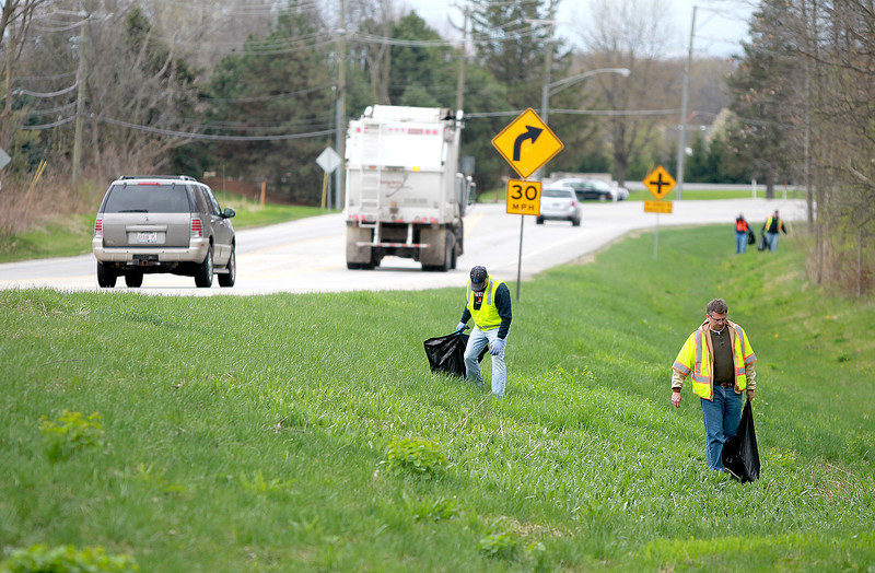 Engineering Enterprises Inc. employees Mark Scheller (right) and Jeff Freeman (left) pick up trash along Bliss Road in Sugar Grove Friday afternoon as part of the Adopt-A-Highway program