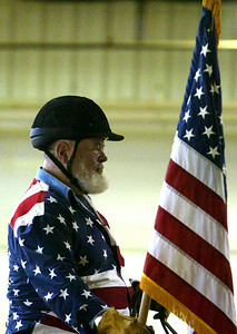 H. Rick Bamman - hbamman@shawmedia.com Veteran John Pavlak carries the flag during the National Anthem at the start of the The 5th Annual BraveHearts Heroes on Horseback horse show