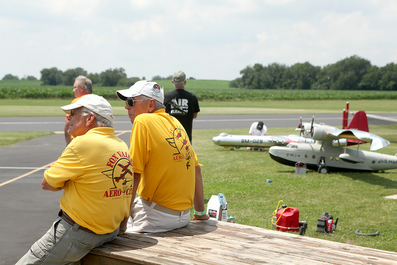 Members of the Fox Valley Aero Club watch as classic planes take flight Friday at the Fox Valley Aero Club field in St. Charles. The event runs through today.