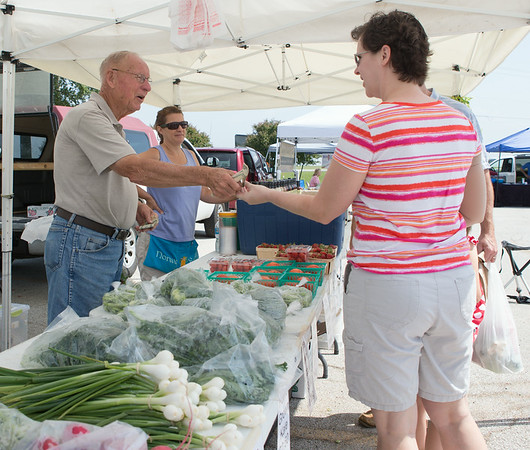 Kim Warren (left) of Sugar Grove, IL completes a purchase of tomatoes from Milt Westlake of Norway Farms from Norway, IL at The Sugar Grove Farmers Market Sugar Grove Village Hall Parking Lot Rt. 30 & Municipal Drive (10 Municipal Drive) in Sugar Grove, IL on Saturday, June 21, 2014 (Sean King for Shaw Media)