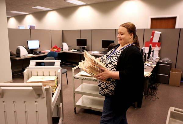 Brie Simkulet, an intern in the Kane County Public Defender office, loads files to be scanned. The office has 96,963 files that need to be eradicated. The paperwork amounts to 406,916 pounds and is stored in break rooms, file rooms, in corners, on bookshelves in various buildings.