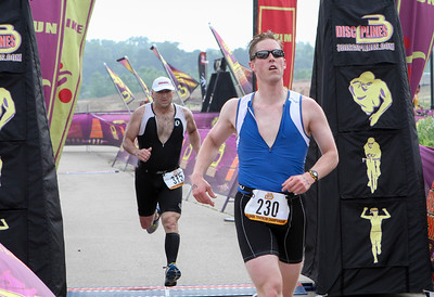 Mike Greene - For Shaw Media Chandler Benton, right of Crystal Lake, crosses the finish line with Jim Stoffel, of St. Charles just behind during the second annual Illinois Championship Triathlon Sunday, June 21, 2015 at the Three Oaks Recreation Area in Crystal Lake.