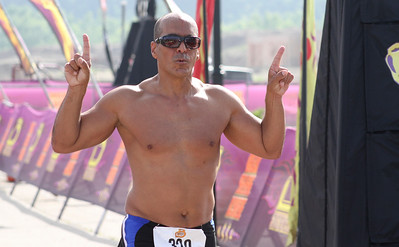 Mike Greene - For Shaw Media Pablo Matias, of Algonquin, celebrate after crossing the finish line during the second annual Illinois Championship Triathlon Sunday, June 21, 2015 at the Three Oaks Recreation Area in Crystal Lake.