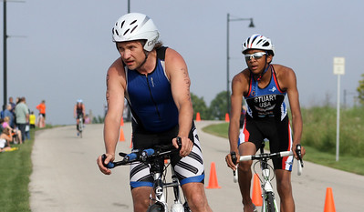 Mike Greene - For Shaw Media Kris Muskala, left of Crystal Lake, and Elijah Stuart, of Gilberts, coast to the end of the bike portion during the second annual Illinois Championship Triathlon Sunday, June 21, 2015 at the Three Oaks Recreation Area in Crystal Lake.