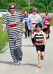 Candace H. Johnson Robert Kilkenny, of Gurnee and his daughter, Jade, 7, run the 5K together during the Outrun the Cops! & Walk for the Kids at the Gurnee Police Department.