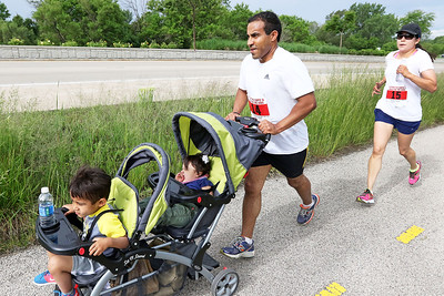 Candace H. Johnson Dan and Martha Arends, of Mundelein run with their children on the path along Washington Street during the Outrun the Cops! & Walk for the Kids at the Gurnee Police Department.