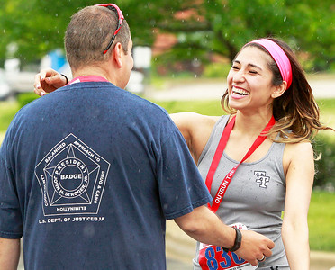 Candace H. Johnson Luis Albarran, of Gurnee gets a hug from his fiancee, Brenda, in the rain after finishing the race during the Outrun the Cops! & Walk for the Kids at the Gurnee Police Department.
