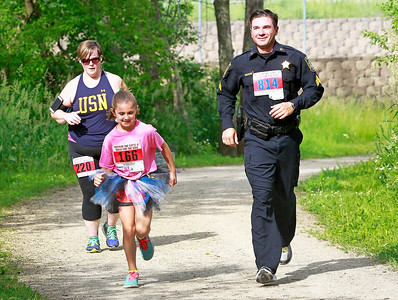 Candace H. Johnson Heather Tobin, of Lake Zurich runs behind Clara O'Brien, 10, and her father, Sgt. Mark O'Brien, with the Gurnee Police Department, during the Outrun the Cops! & Walk for the Kids at the Gurnee Police Department.