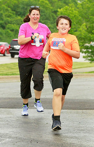 Candace H. Johnson Lake Zurich Police Officer, Denise Bradstreet, runs with her son, Jake, 10, towards the finish line during the Outrun the Cops! & Walk for the Kids at the Gurnee Police Department.