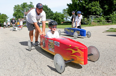 Mike Greene - For Shaw Media  Gabe Winkleman, 8 of McHenry gets some help from his dad Joe heading towards the starting line during the 14th Annual McHenry Kiwanis All-American 2016 Soap Box Derby Saturday, June 11, 2016 in McHenry.