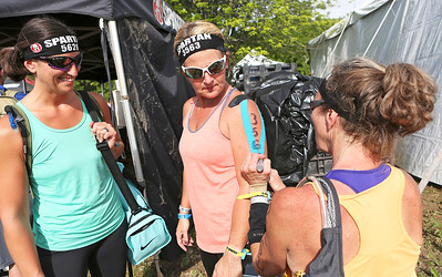 Mike Greene - For Shaw Media  Roona Moore, center, receives help with her bib number from Lorrie Headley, right, as Becky Williamson watches on before the start of their heat of the Spartan Race: Chicago Super 2016 Saturday, June 11, 2016 at the Richmond Hunt Club in Richmond.
