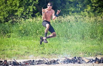 Mike Greene - For Shaw Media  A competitor strikes a pose while jumping over fire during the Spartan Race: Chicago Super 2016 Saturday, June 11, 2016 at the Richmond Hunt Club in Richmond.