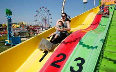 Jessica Cannon, from Algonquin, and her son Logan, 1, take a ride on the Power Slide at Harvard's Milk Days on Saturday, June 3, 2017 in Harvard. John Konstantaras photo for the Northwest Herald