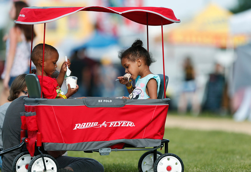 (L-R) Twins Nini and Gabby, both 4 from Rockford, enjoy their ice cream at Harvard's Milk Days on Saturday, June 3, 2017 in Harvard. John Konstantaras photo for the Northwest Herald