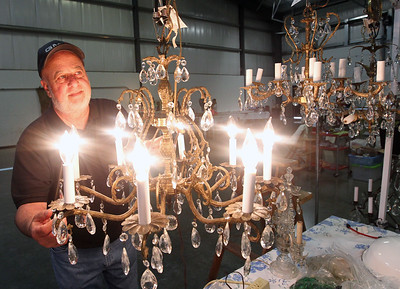 Candace H. Johnson-For Shaw Media Dan Constantino, of Grayslake looks at one of the chandeliers he had for sale at the Grayslake Antique & Vintage Market at the Lake County Fairgrounds in Grayslake.