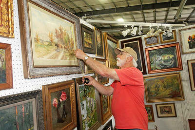 Candace H. Johnson-For Shaw Media Doug McEnroe, of Fennville, Mich., measures an original watercolor by artist Thomas Bigelow Craig in his booth at the Grayslake Antique & Vintage Market at the Lake County Fairgrounds in Grayslake.