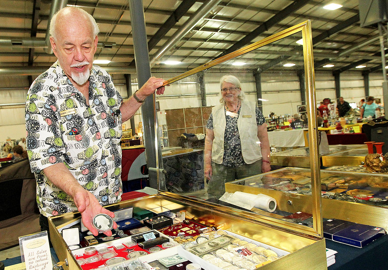 Candace H. Johnson-For Shaw Media Robert Hanson, of Richfield, Wis., with Numismatic Investments, shows a five-ounce pure silver Buffalo coin he has for sale as his wife, Caren, stands close by at the Grayslake Antique & Vintage Market at the Lake County Fairgrounds in Grayslake.