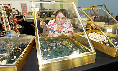 Candace H. Johnson-For Shaw Media Ellen Germanos, of Arlington Heights shows a necklace from one of her glass cases at the Grayslake Antique & Vintage Market at the Lake County Fairgrounds in Grayslake.
