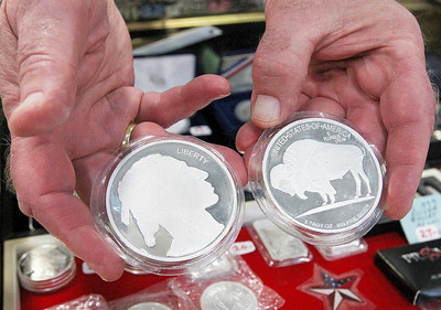 Candace H. Johnson-For Shaw Media Robert Hanson, of Richfield, Wis., with Numismatic Investments shows two five-ounce Buffalo coins he had for sale at the Grayslake Antique & Vintage Market at the Lake County Fairgrounds in Grayslake.