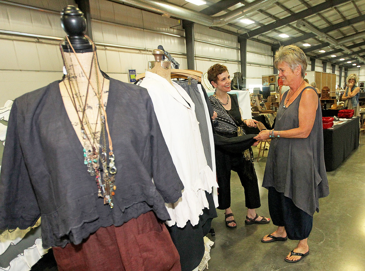 Candace H. Johnson-For Shaw Media Jane Tallman, of Wadsworth (on right) with Sunrags Studio shows Stacy Litow of Highland Park some clothes she was selling at the Grayslake Antique & Vintage Market at the Lake County Fairgrounds in Grayslake.