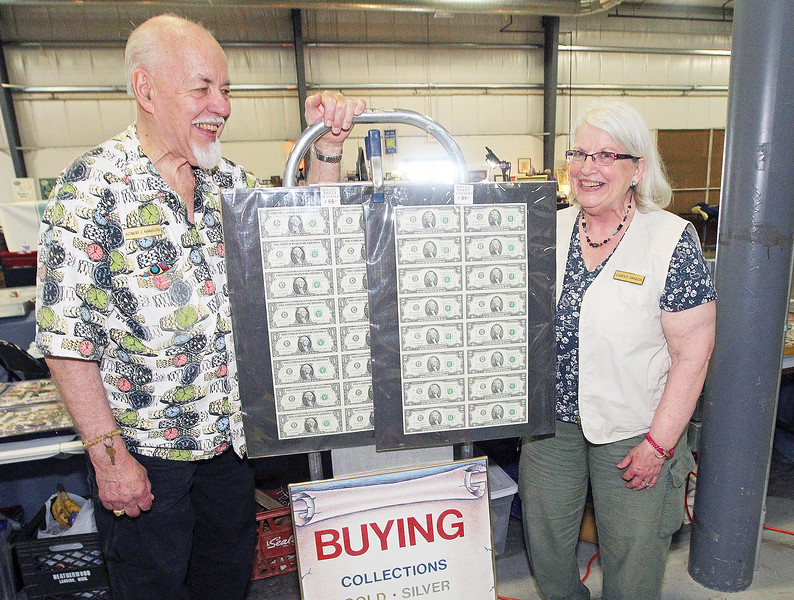 Candace H. Johnson-For Shaw Media Robert and Caren Hanson, of Richfield, Wis., with Numismatic Investments stand next to half sheets of one and two dollar bills they were selling at the Grayslake Antique & Vintage Market at the Lake County Fairgrounds in Grayslake. The Hanson's have been married for fifty-one years.