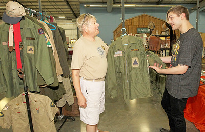 Candace H. Johnson-For Shaw Media Jim Tamraz, of Grayslake with Militaria, talks with Adrian-Thorvald Windsor, 21, of Winnetka about one of the of the U.S. Army jackets he had for sale from the 1960's during the Grayslake Antique & Vintage Market at the Lake County Fairgrounds in Grayslake. The military jacket belonged to Tamraz's father, John.