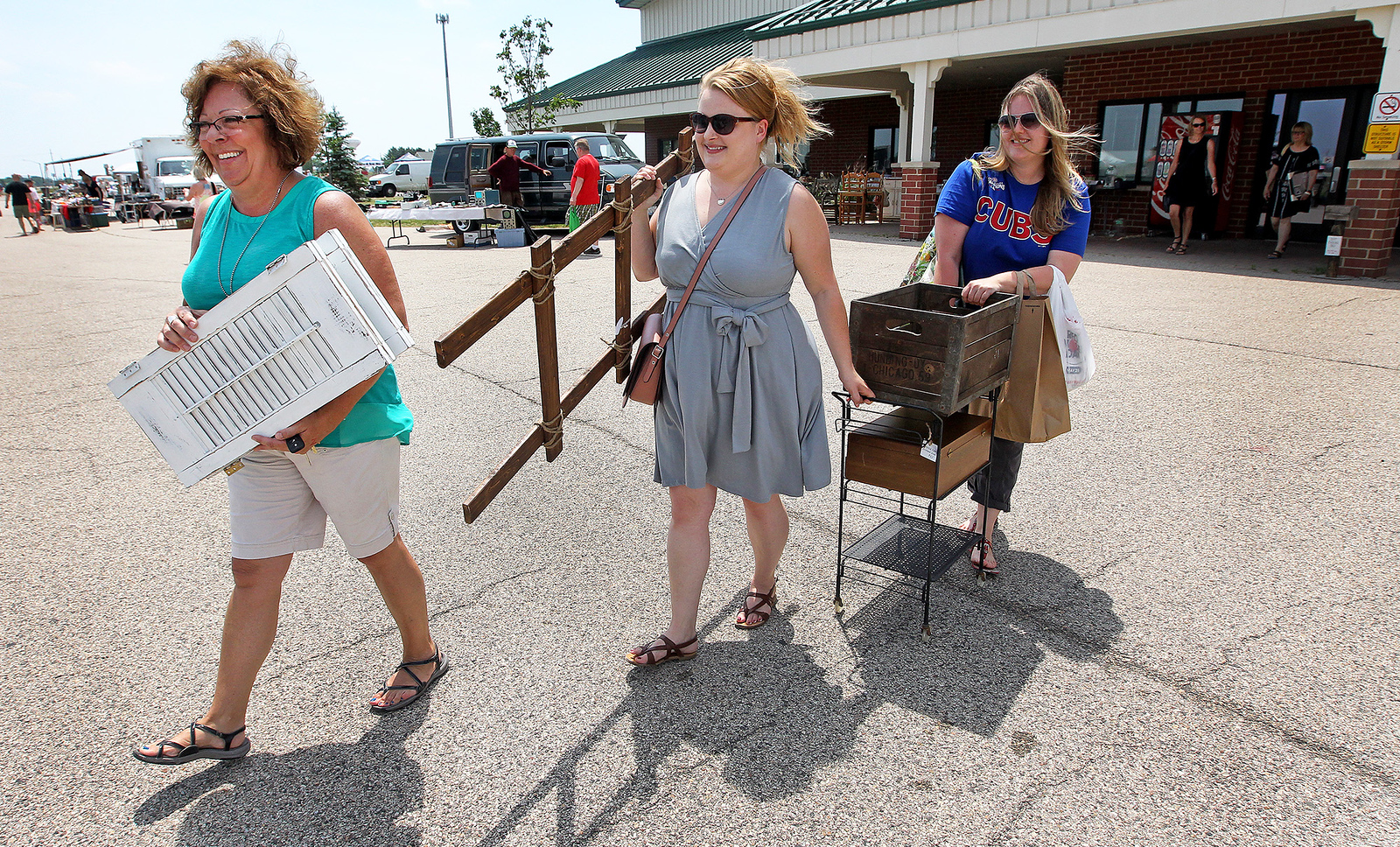 Candace H. Johnson-For Shaw Media Diane Wolanik, her daughter-in-law Jennifer, both of Crystal Lake, and Stephanie Knudson, of Lake Zurich head to their car with some items they bought at the Grayslake Antique & Vintage Market at the Lake County Fairgrounds in Grayslake.