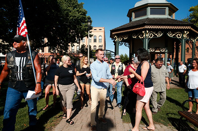 Marine Recon Sergeant Jared Fringer, center, a 2007 Woodstock HS alum, gets an escort to the Woodstock Square gazebo where he was surprised with a welcome home ceremony honoring the local hero on Friday, June 16, 2017 in Woodstock, Illinois. John Konstantaras photo for the Northwest Herald
