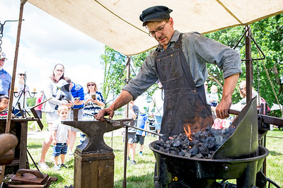 "Mike Greene - For Shaw Media  Sam Johnson, of Lakemoor, operates a blacksmith booth during the 10th annual ""A Day at Petersen Farm"" Sunday, June 25, 2017 in McHenry. This year's event featured hayrides, farm animals, music and children's games as well as exhibits showing McHenry County farm life in 1916."