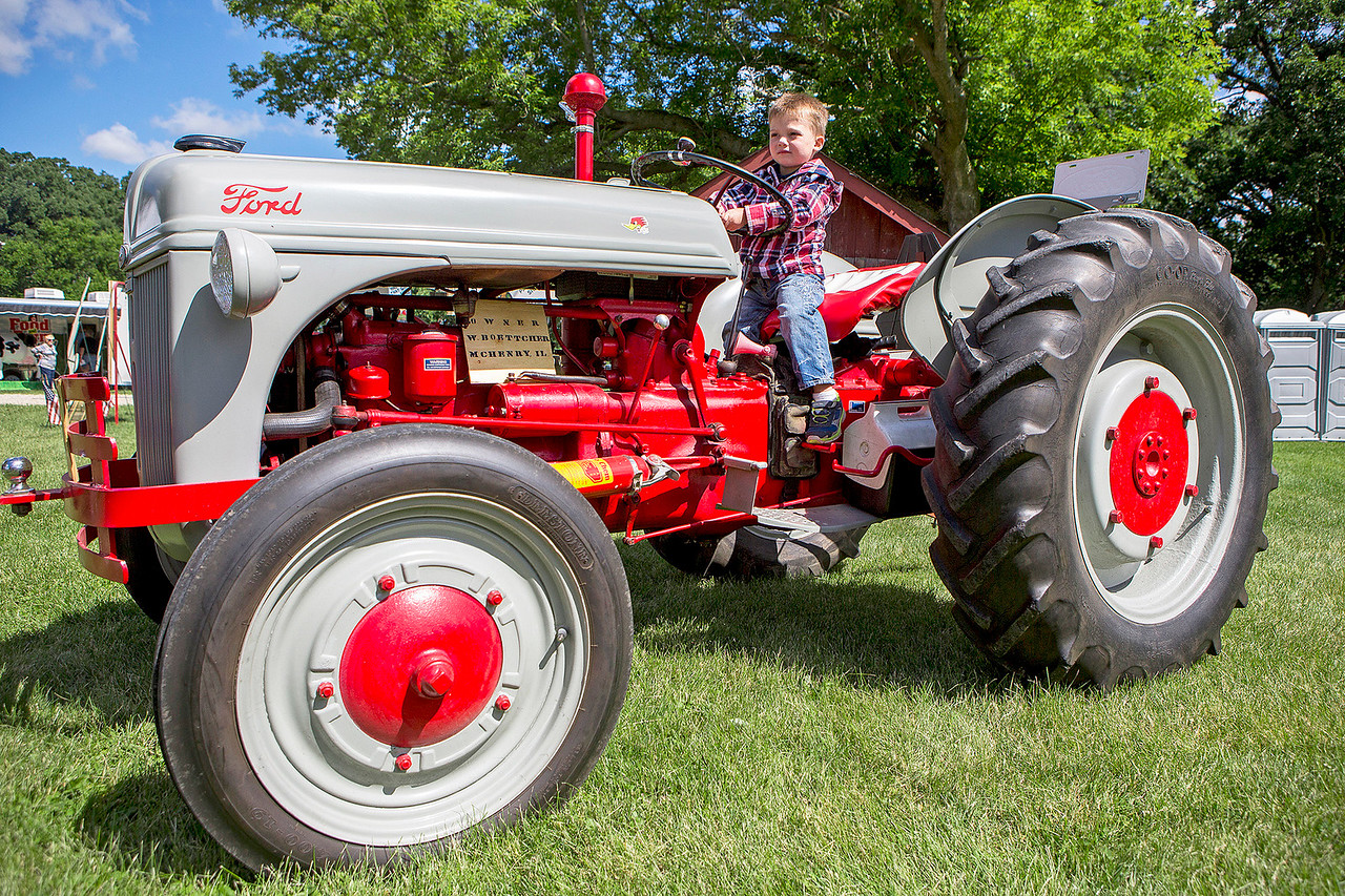 "Mike Greene - For Shaw Media  Thomas Stamatis, 3 of McHenry, tests out a 1941 Ford 9N provided by Walt Boettcher during the 10th annual ""A Day at Petersen Farm"" Sunday, June 25, 2017 in McHenry. This year's event featured hayrides, farm animals, music and children's games as well as exhibits showing McHenry County farm life in 1916."