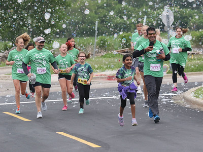 Candace H. Johnson-For Shaw Media Runners get through a wall of bubbles during the Squeez'd Girls on the Run North 5K at the College of Lake County in Grayslake.(6/2/18)