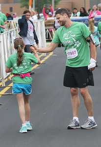Candace H. Johnson-For Shaw Media Addison Filipowicz, 9, of Gurnee is congratulated by her father, Mike, after they both crossed the finish line during the Squeez'd Girls on the Run North 5K at the College of Lake County in Grayslake.(6/2/18)