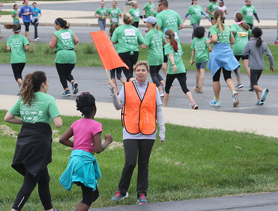 Candace H. Johnson-For Shaw Media Volunteer Ruthanne Hall, of Mundelein, a course marshall, keeps the runners on track and encourages them during the Squeez'd Girls on the Run North 5K at the College of Lake County in Grayslake.(6/2/18)